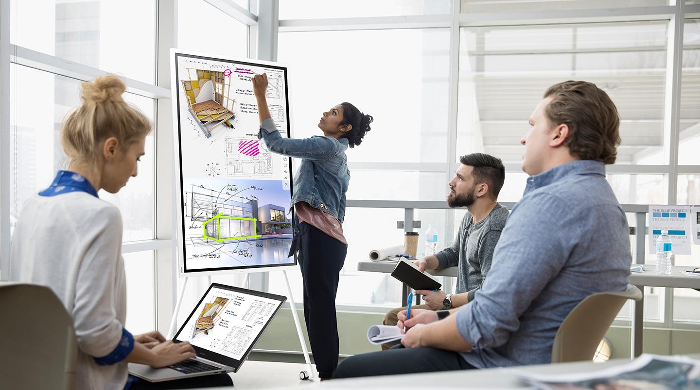 VIDELIO x Samsung Dans un open space, brainstorming entre 4 personnes. L'une annote une image sur le Flip, une autre récupère les informations sur son PC