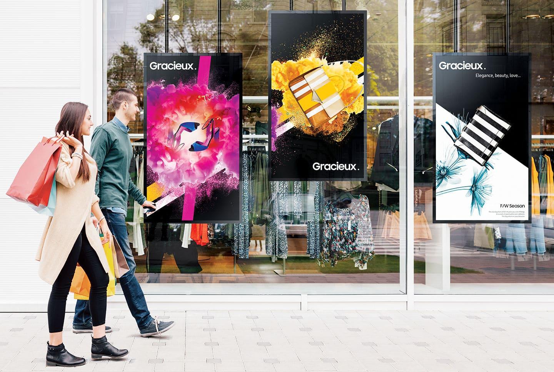 VIDELIO x Samsung Des passants regardent la vitrine d'un magasin où il y a 3 écrans verticaux